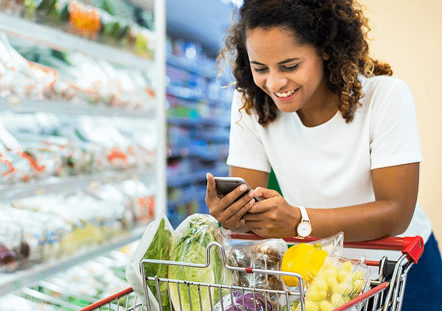 woman holding a cellphone while grocery shopping